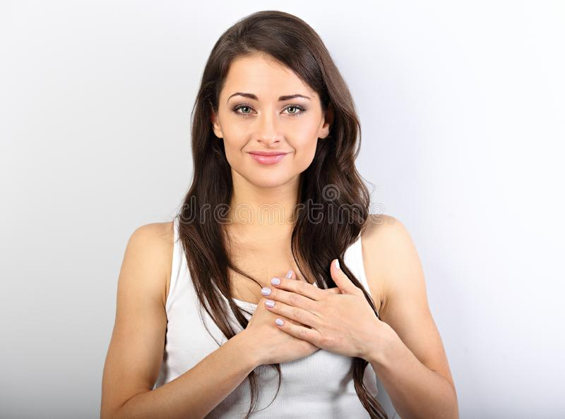 Beautiful woman in love holding herself chest and heart two hands with enjoying smiling face and thinking about emotion. Relationship. Closeup portrait royalty free stock photo