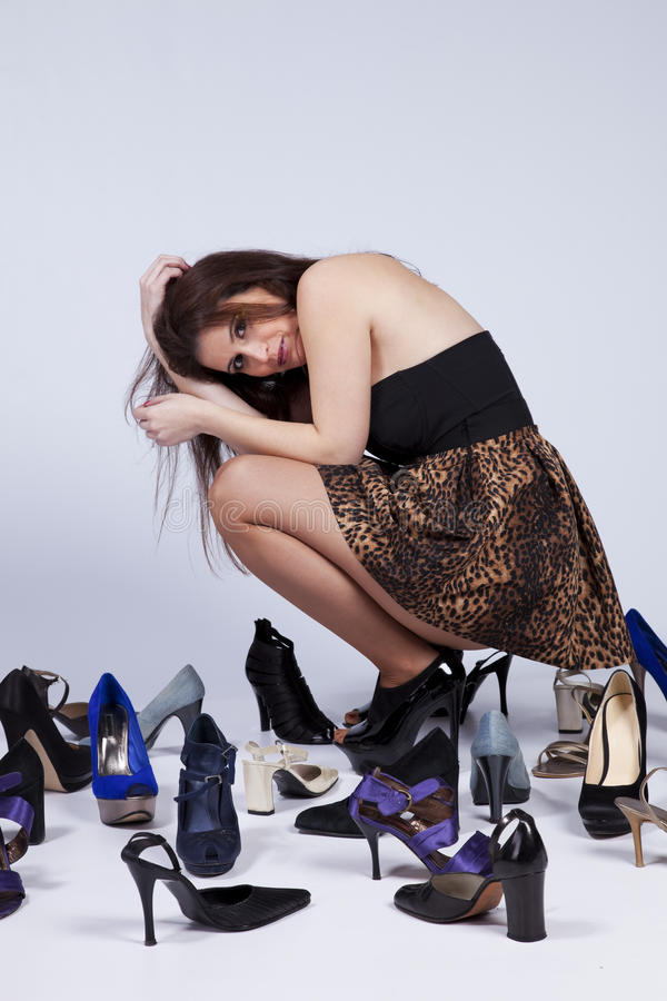 Beautiful woman that loves shoes. Happy young woman surrounded by all of her shoes royalty free stock image