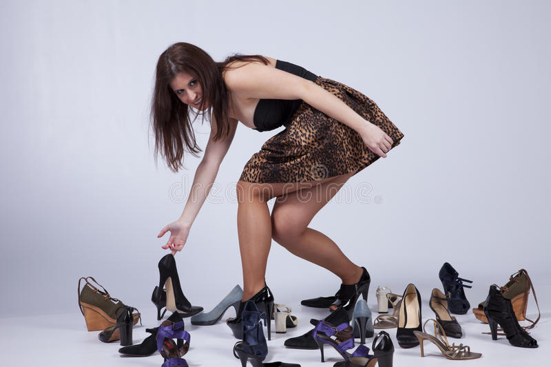 Beautiful woman that loves shoes. Happy young woman surrounded by all of her shoes royalty free stock photo