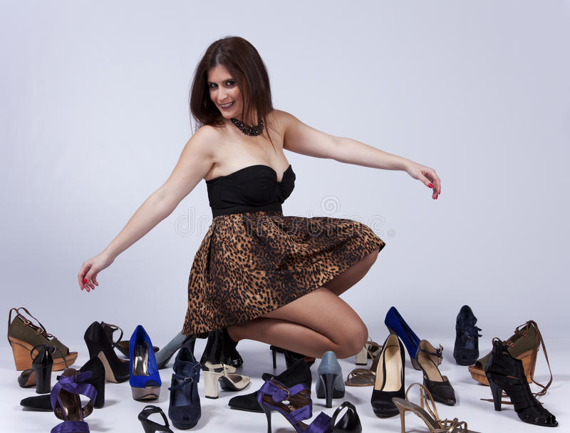 Beautiful woman that loves shoes. Happy young woman surrounded by all of her shoes stock image