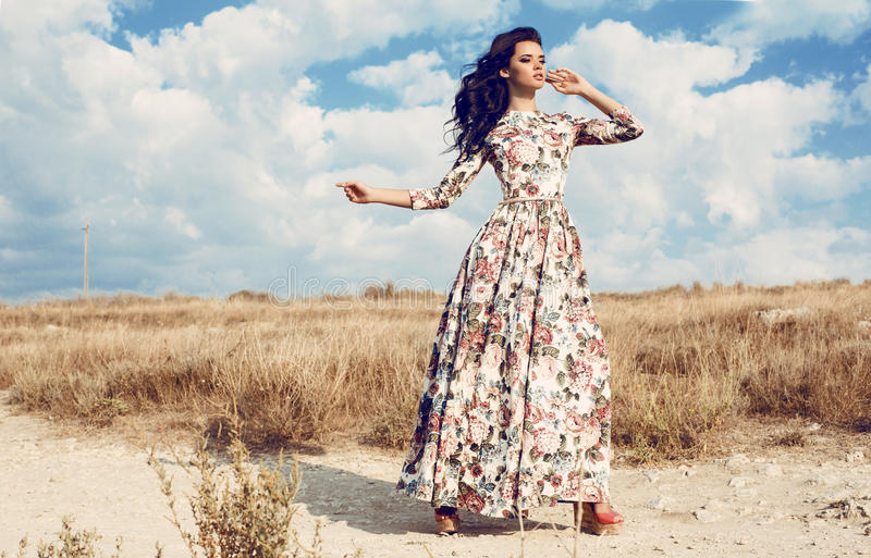 Beautiful woman in luxurious floral dress posing in summer field. Fashion outdoor photo of beautiful woman with dark curly hair in luxurious floral dress posing royalty free stock image