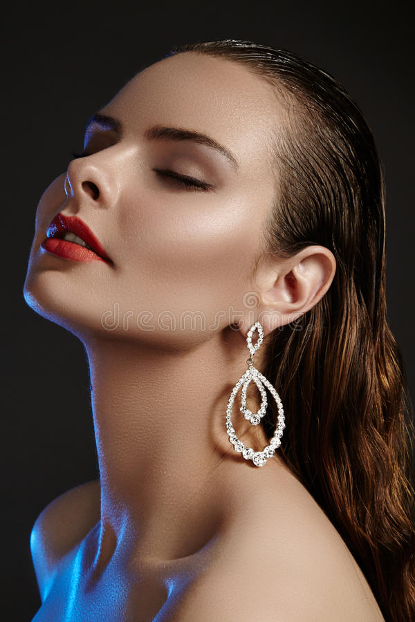 Beautiful woman in luxury fashion earrings. Diamond shiny jewelry with brilliants. Accessories jewelery, fashion makeup. Beautiful woman in luxury fashion royalty free stock images