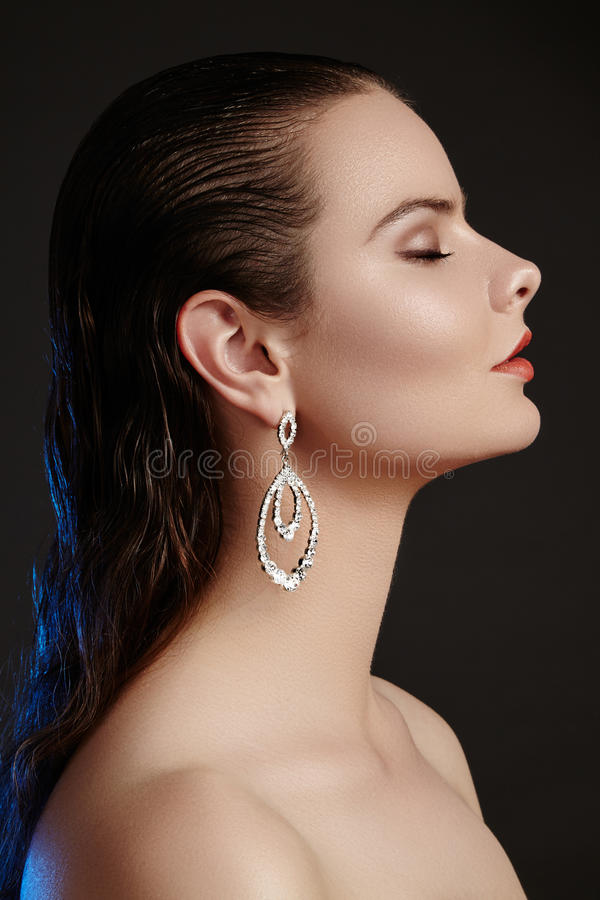 Beautiful woman in luxury fashion earrings. Diamond shiny jewelry with brilliants. Accessories jewelery, fashion makeup. Beautiful woman in luxury fashion royalty free stock photos