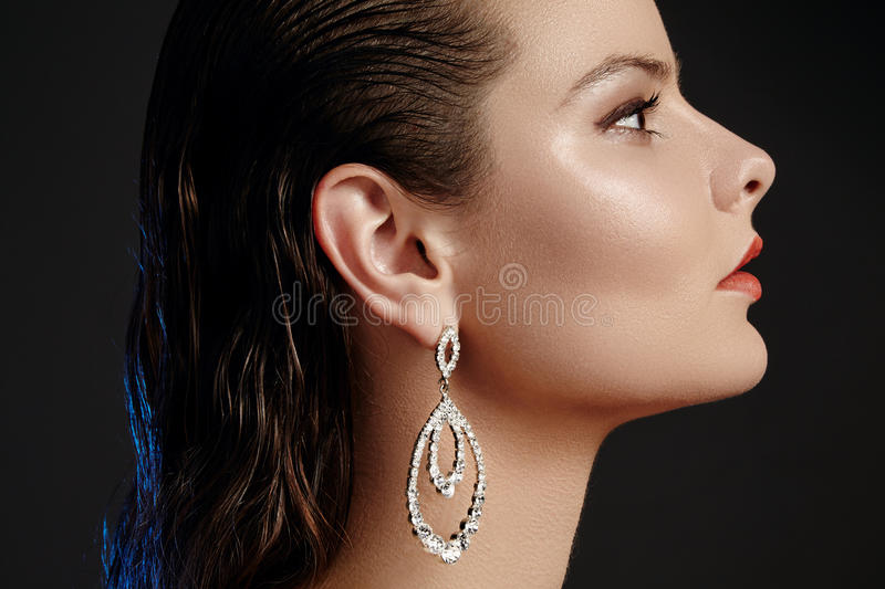 Beautiful woman in luxury fashion earrings. Diamond shiny jewelry with brilliants. Accessories jewelery, fashion makeup. Beautiful woman in luxury fashion royalty free stock image