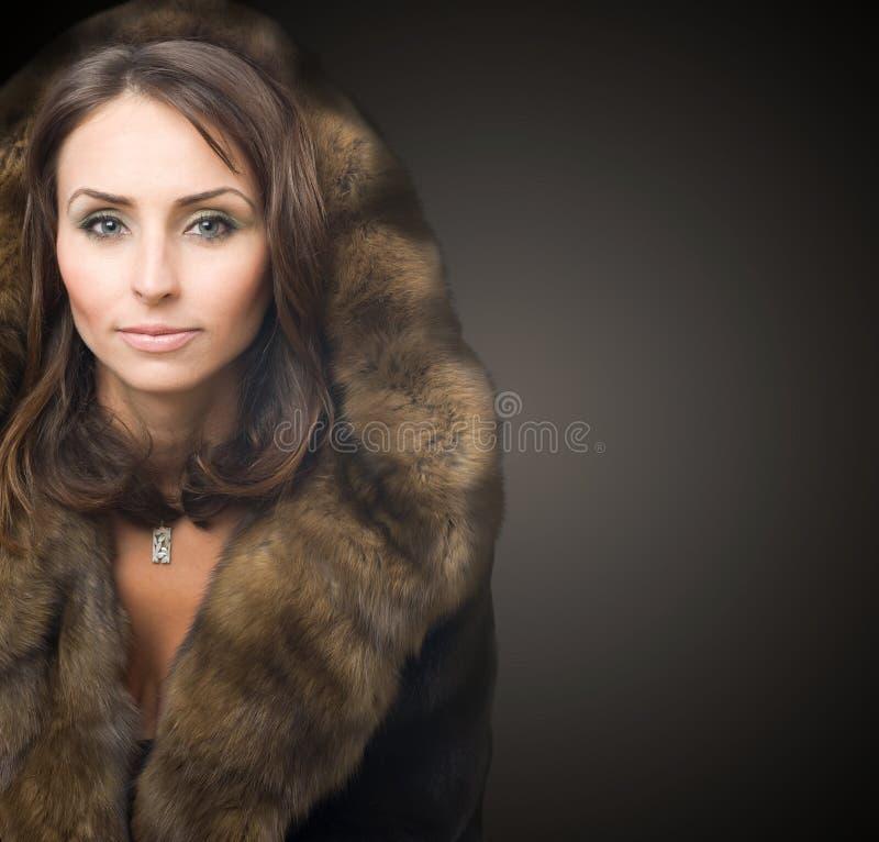 Beautiful woman in luxury fur coat royalty free stock photo