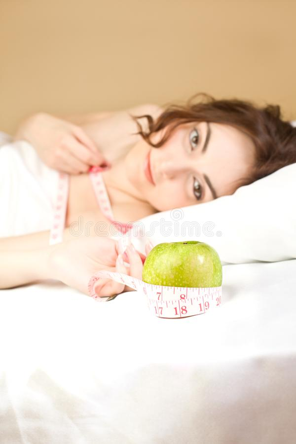 Beautiful woman lying in bed with green apple and tape measure royalty free stock photos