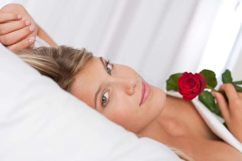 Beautiful woman lying in bed holding red rose stock image