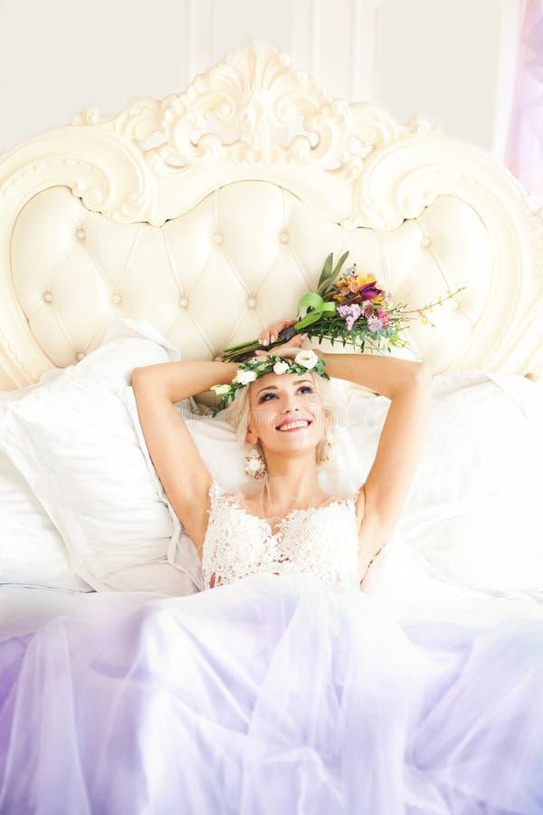 Beautiful Woman Lying di modello sorridente sul letto immagine stock