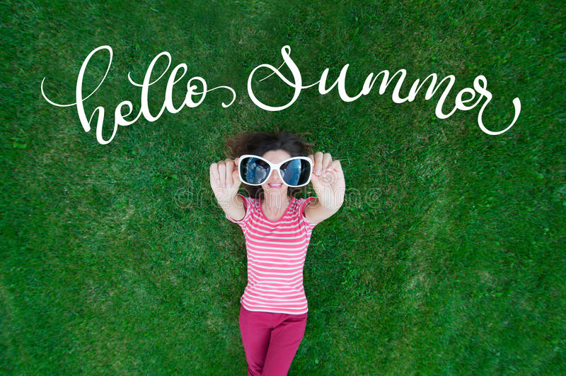 Beautiful woman lying on the grass and holding glasses in his hands. text Hello Summer. Calligraphy lettering.  stock photos
