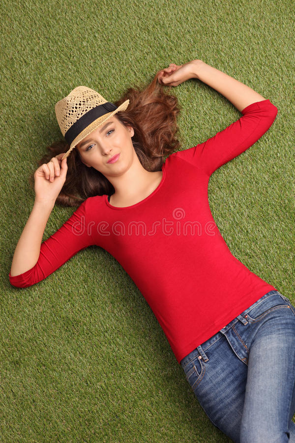 Beautiful woman lying on grass in a meadow royalty free stock photography
