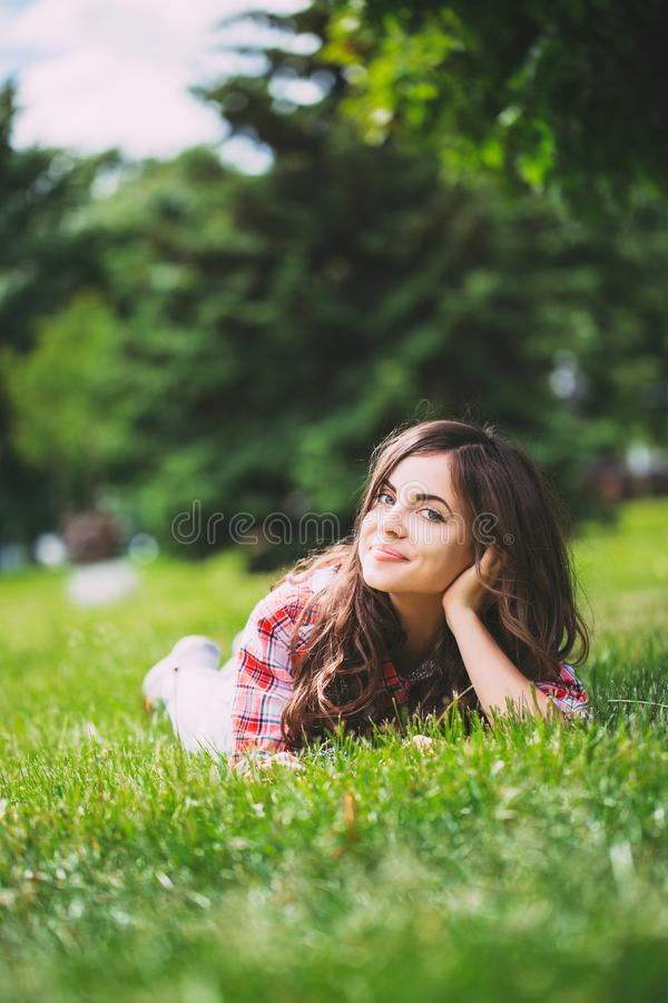 Beautiful woman lying on green grass stock images
