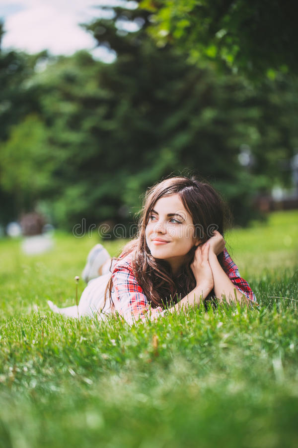 Beautiful woman lying on green grass royalty free stock images