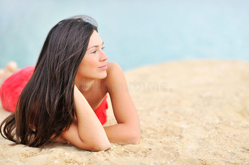 Beautiful woman lying on a sand while looking at copyspace stock photos