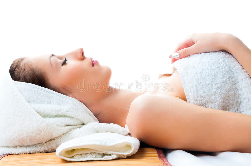 Beautiful woman lying on table in spa salon stock photo