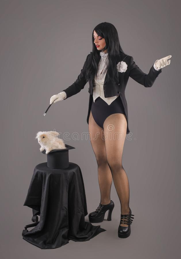 Beautiful woman magician with rabbit in hat stock photo