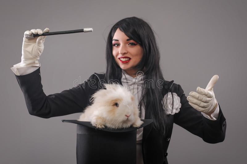 Beautiful woman magician with rabbit in hat stock photos