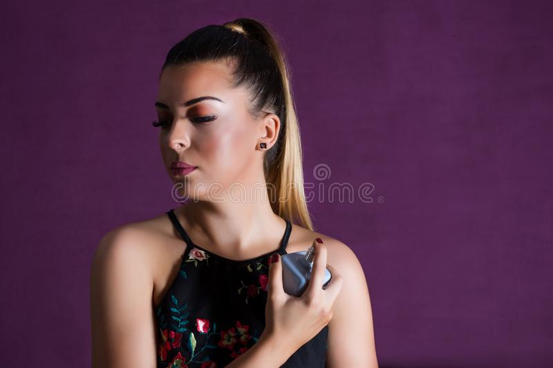 Beautiful woman with make up spraying perfume on her neck on purple background royaltyfria foton