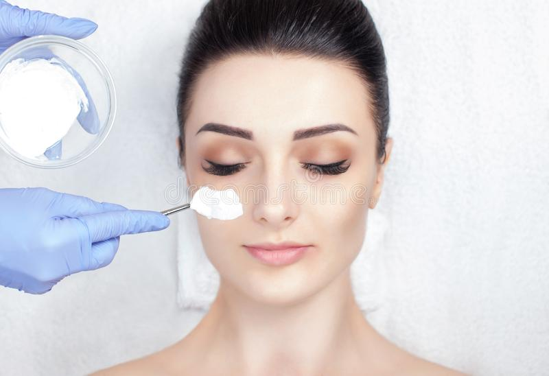 A beautiful woman makes a anti wrinkle mask on her face. Spa treatments and face care in the beauty salon stock photos