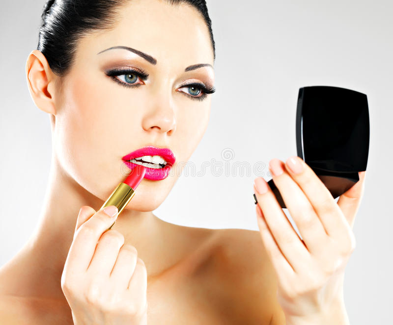 Beautiful woman applying pink lipstick on lips royalty free stock image