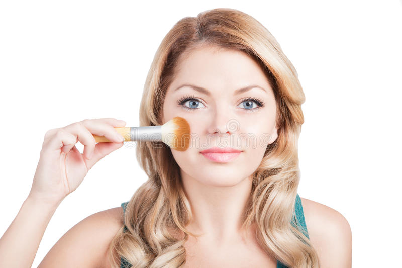 Beautiful woman with Makeup Brush. Young blonde girl is holding make up brush near her pretty face. White background. Studio shot royalty free stock images