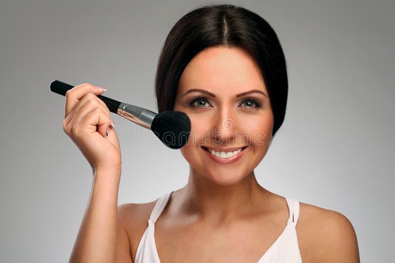 Beautiful woman with makeup brush royalty free stock photo