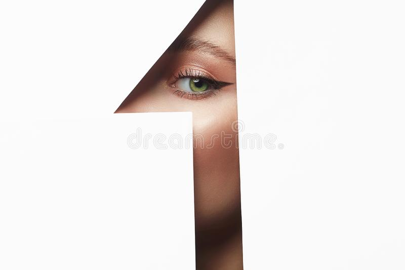 Beautiful woman with makeup into paper hole. Make-up artist concept. arrows on the eyes. number one stock photo