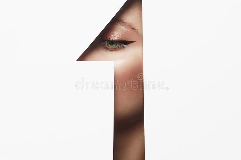 Arrows on the eyes. make-up artist concept. Beautiful woman with makeup into paper hole. make-up artist concept. arrows on the eyes. number one stock image