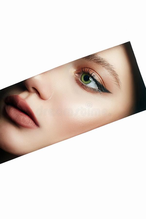Beautiful woman with makeup into paper hole. Young beautiful woman with makeup into paper hole. make-up artist concept. arrows on the eyes royalty free stock image