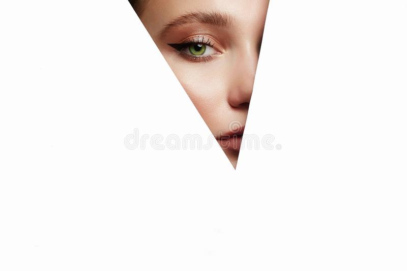 Beautiful woman with makeup into paper hole. Young beautiful woman with makeup into paper hole. make-up artist concept. arrows on the eyes stock image