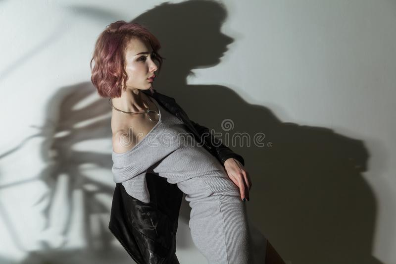 Beautiful woman with makeup and short pink hair in grey dress and black leather jacket posing on grey background with dark shadow stock images