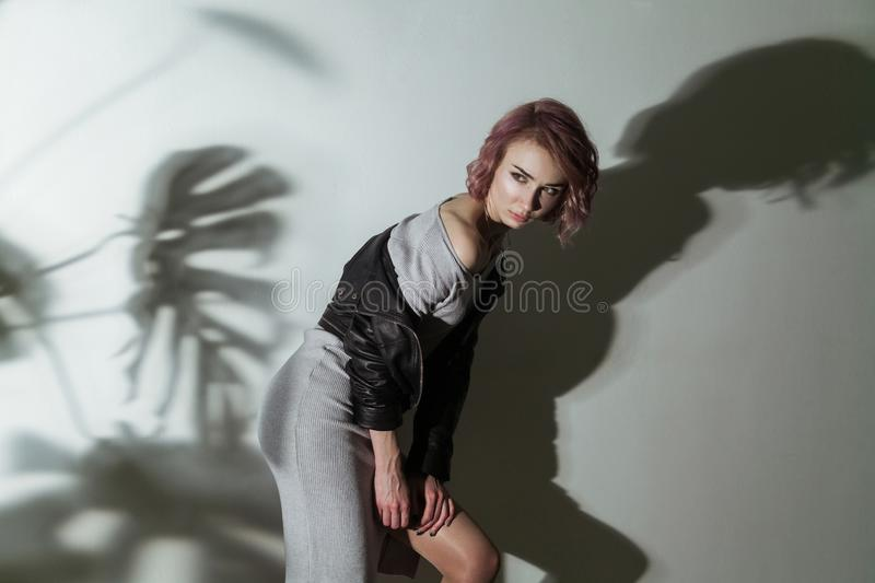 Beautiful woman with makeup and short pink hair in grey dress and black leather jacket posing on grey background with dark shadow royalty free stock photo