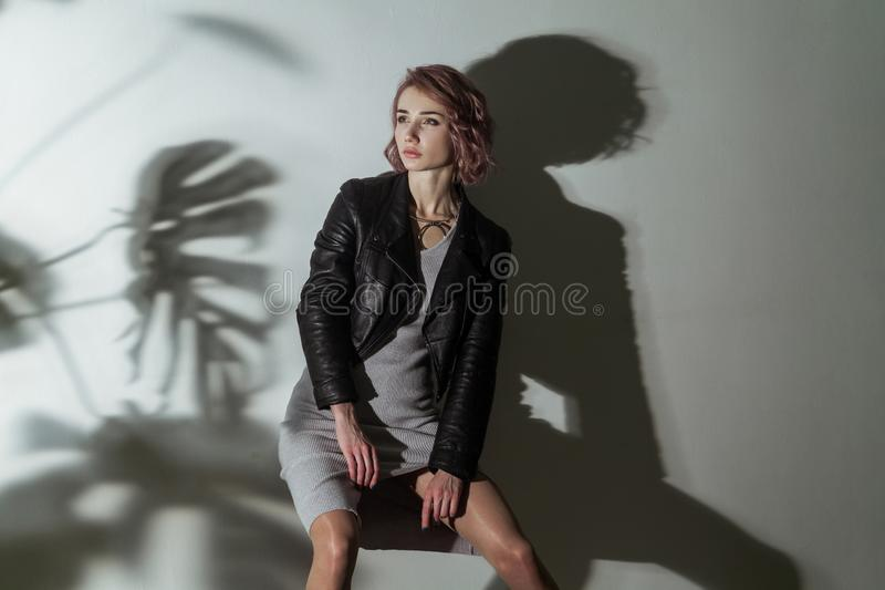 Beautiful woman with makeup and short pink hair in grey dress and black leather jacket posing on grey background with dark shadow royalty free stock image