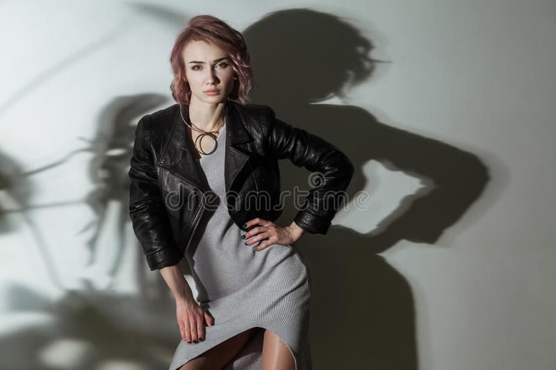 Beautiful woman with makeup and short pink hair in grey dress and black leather jacket posing on grey background with dark shadow royalty free stock photography