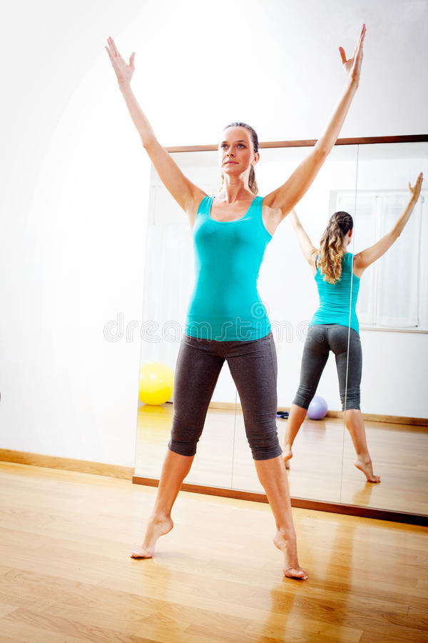 Beautiful woman making fitness exercises stretching witn open arms. Young woman making fitness exercises stretching witn open arms stock images