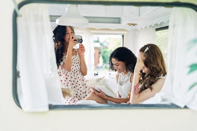 Beautiful woman making photo of her multi ethnic friends inside the camper van during their summer travel stock photos