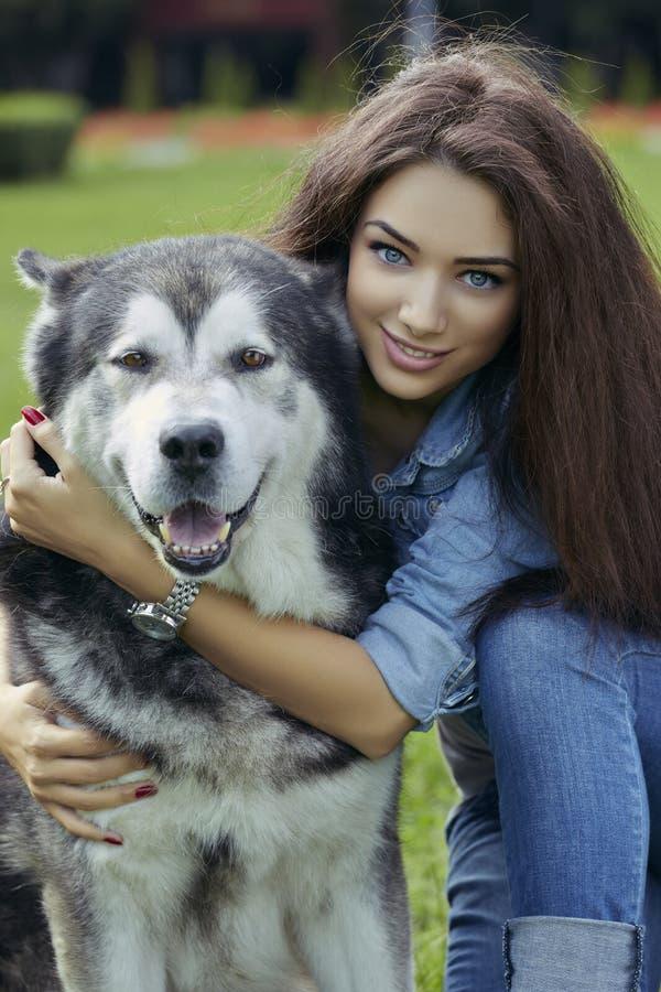 Beautiful woman with Malamute dog stock photo