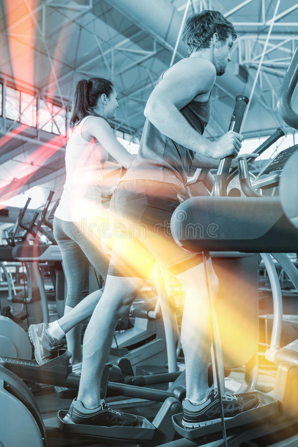 Beautiful woman and man exercising on elliptical machine royalty free stock image