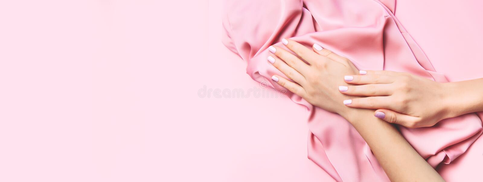 Beautiful woman manicure on creative pink background with silk fabric. Minimalist trend royalty free stock photography