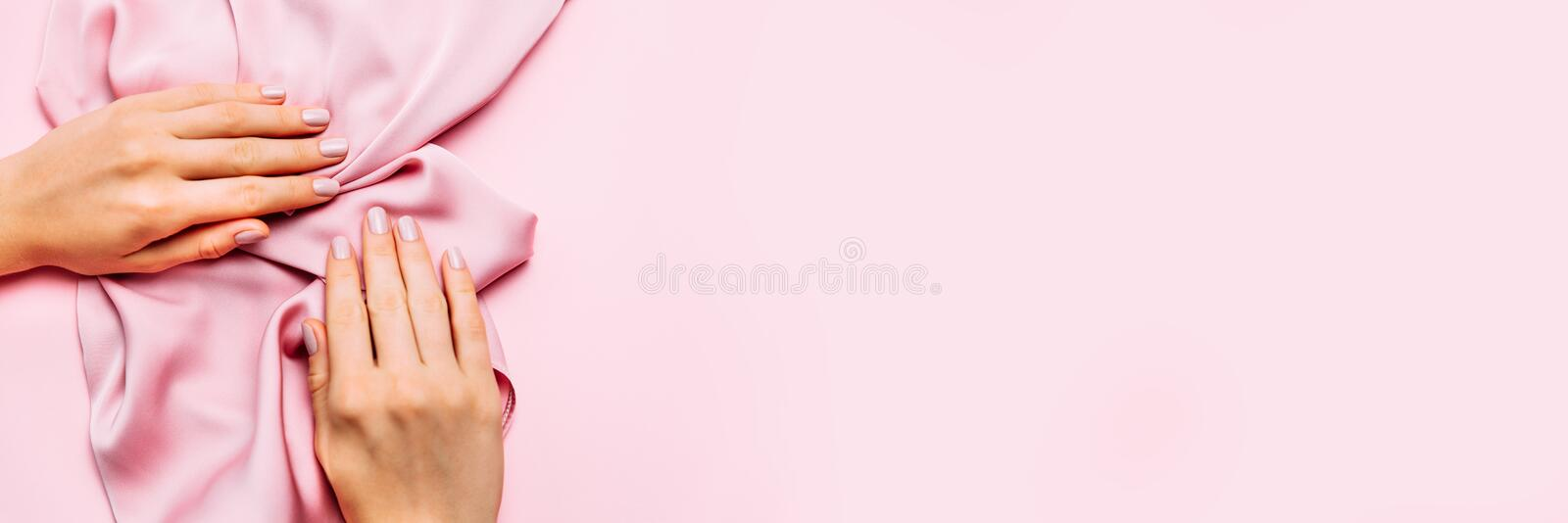 Beautiful woman manicure on creative pink background with silk fabric. Minimalist trend royalty free stock image