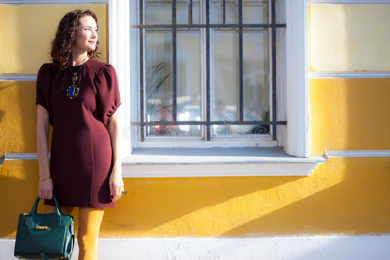 Beautiful woman in a maroon dress. Near the wall of old house with a window. fashion image royalty free stock photos