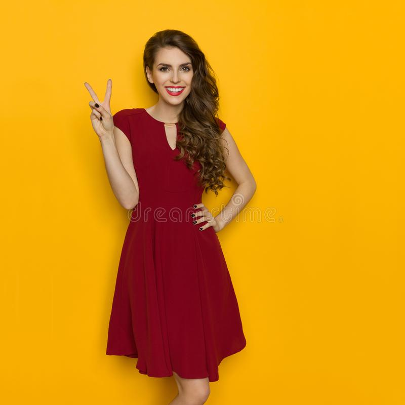Beautiful Woman In Maroon Dress Is Showing Peace Hand Sign. Smiling attractive woman in maroon dress is posing with hand on hip and showing peace hand sign stock images