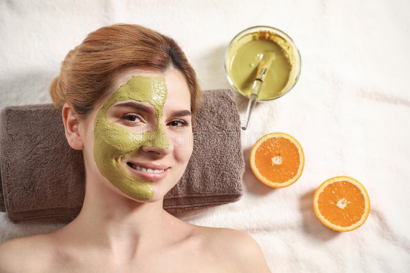 Beautiful woman with mask on face relaxing, top view. Beautiful woman with mask on face relaxing in spa salon, top view stock photo