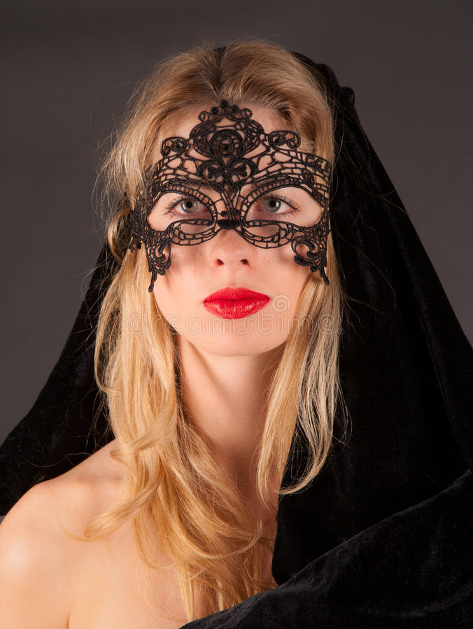 Beautiful Woman in Mask. A portrait of a gorgeous young woman in a lace mask with red lipstick royalty free stock photos