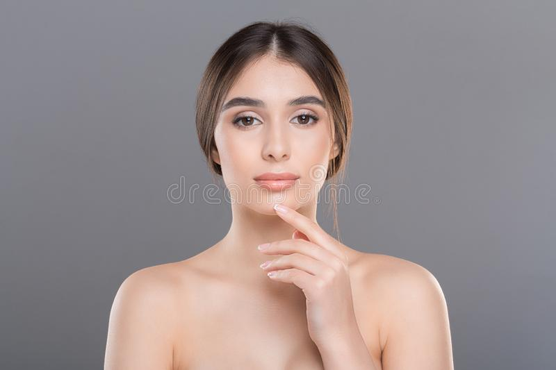 Beautiful woman massaging her face, grey background. Facial contouring. Beautiful woman massaging her face, grey studio background royalty free stock photo