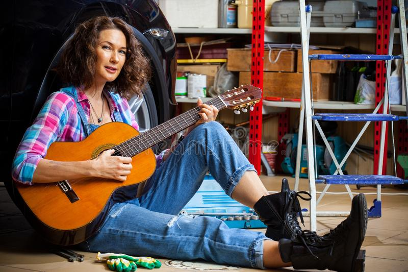 Beautiful Woman mechanic in blue overalls resting with a guitar stock photos