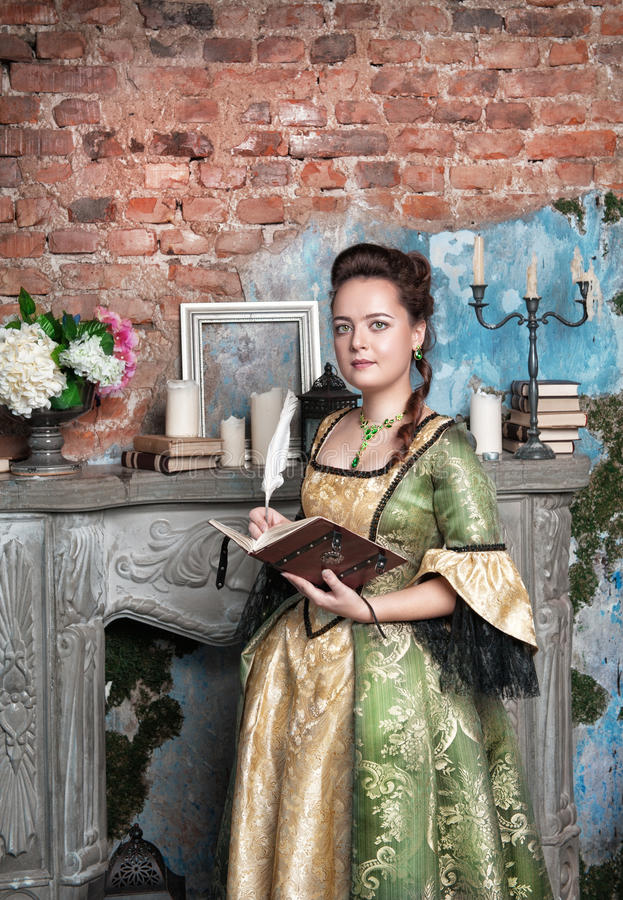Beautiful woman in medieval dress with book and feather royalty free stock photography