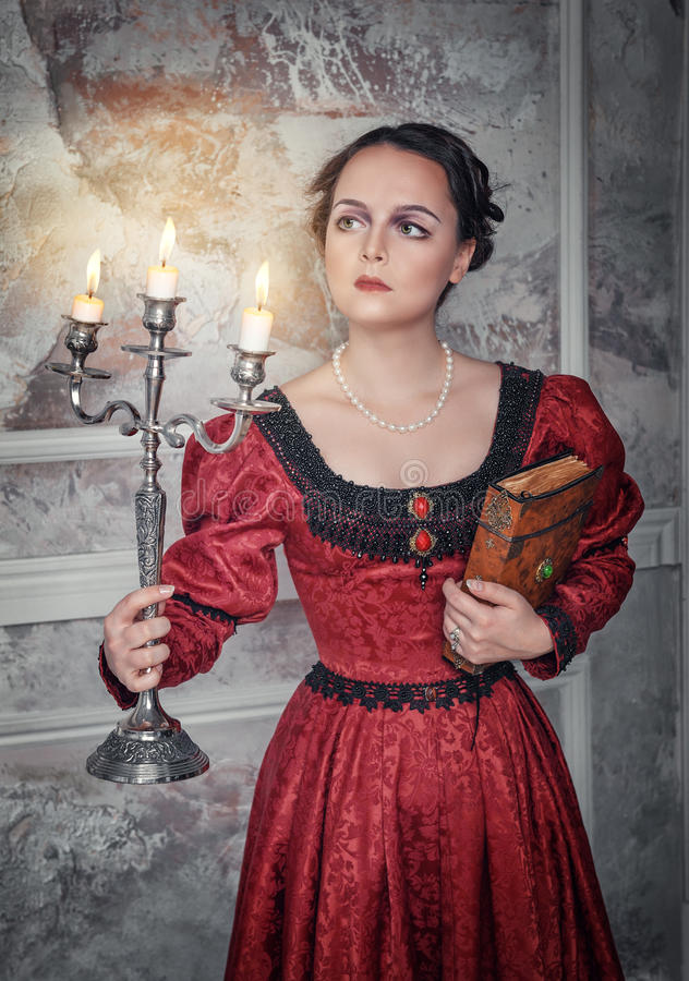 Beautiful woman in medieval dress with candelabrum. Beautiful young woman in long red medieval dress with candelabrum and book royalty free stock photo