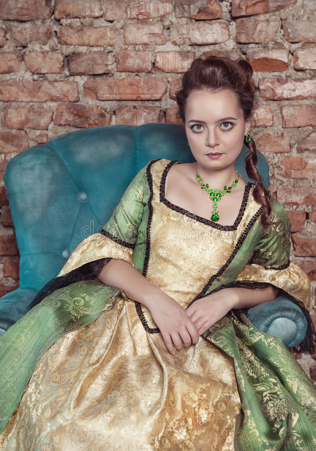 Beautiful woman in medieval dress. Portrait of beautiful woman in medieval dress sitting on the sofa stock images