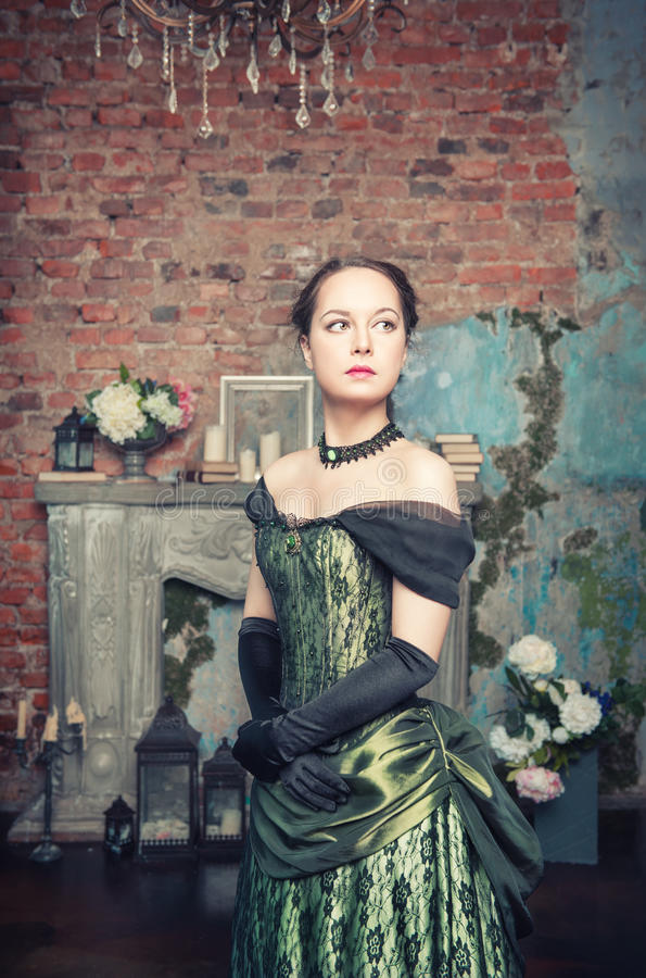 Beautiful woman in medieval dress. Beautiful young woman in long green medieval dress in the room royalty free stock image