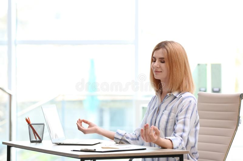 Beautiful woman meditating at table in office during break. Zen yoga royalty free stock photo
